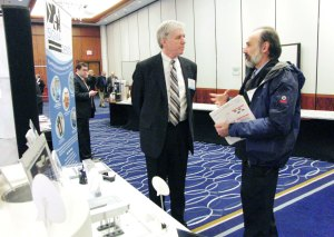 Jerry Lynch, left, President of Sigma Design Company talks with an attendee at conference.